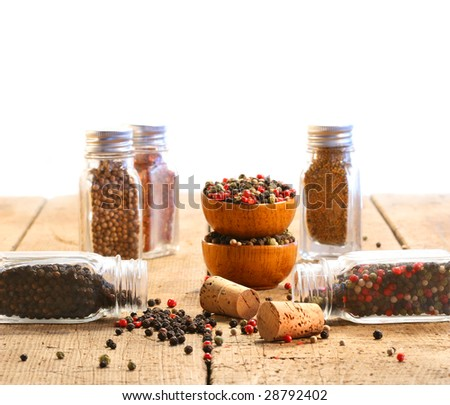 Spice glass containers on old wood table with white background - stock photo