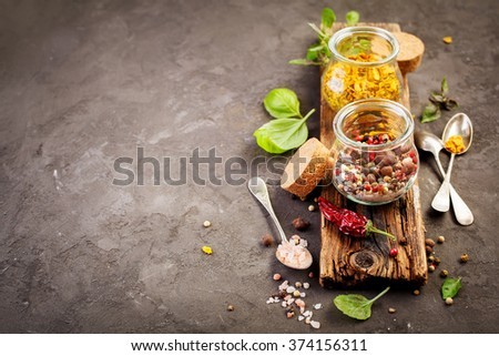 Spice mix and ingredients for cooking, red pepper, black pepper, white pepper, hot pepper, basil and salt. Rustic background with copy space - stock photo