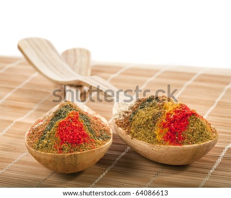 spice powder mix in a wooden spoon on a bamboo napkin - stock photo