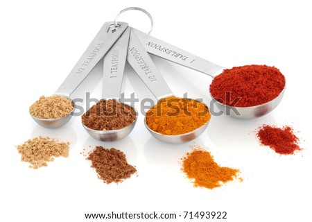 Spice selection of paprika, turmeric, chinese five spice and  ginger in stainless steel measuring spoons, and loose, over white background. Right to left. Selective focus. - stock photo
