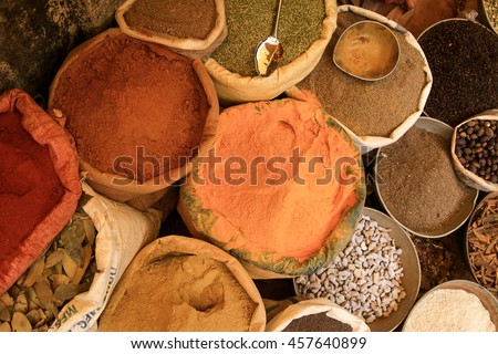 Spice vendor's display in market of colorful powdered spices, ayurvedic herbs, etc. - stock photo