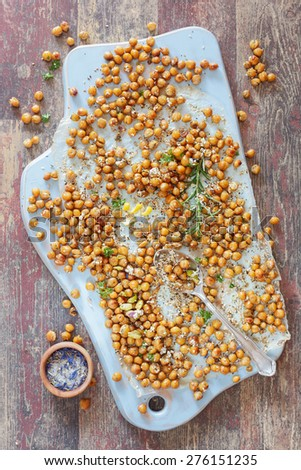 Spiced chickpeas. Spicy Oven Roasted Chickpeas on a wooden board, rustic  wooden background, vintage style.  Natural light - stock photo