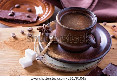 Spiced coffee in a textured ceramic cup with cinnamon powder, anise stars, sugar and pieces of chocolate over wooden table closeup. Selective focus, shallow depth of field - stock photo
