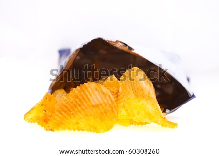 spiced golden chips pile with the bag on white background - stock photo