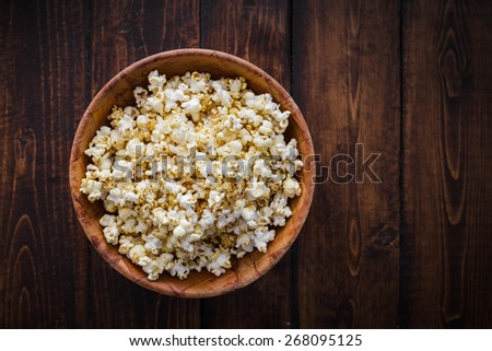 Spiced Popcorn in a Wooden Bowl on a Table in the Living Room - stock photo