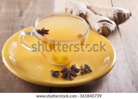 Spiced tea with sea buckthorn and ginger and spices on a yellow plate