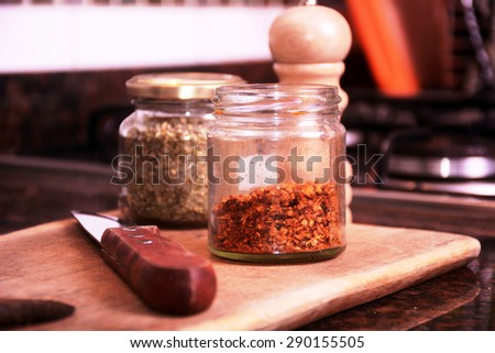 Spices and a knife on a cutting board. Condiments on a kitchen. - stock photo