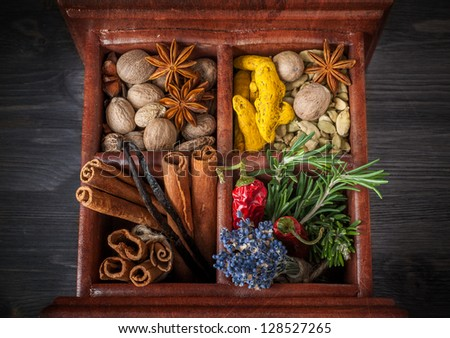 Spices and herbs in a wooden box - stock photo