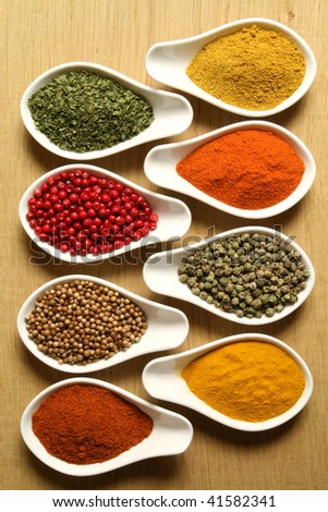 Spices and herbs in white ceramic bowls. Food and cuisine ingredients. Colorful natural additives.