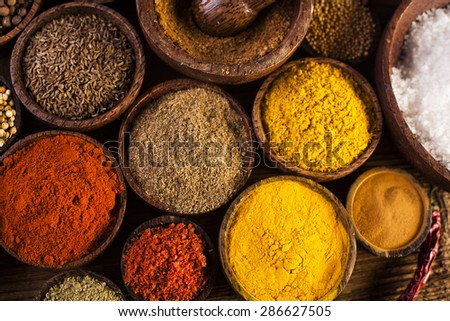 Spices and herbs in wooden bowls - stock photo