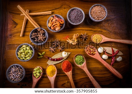 Spices and Herbs in wooden spoons and stone bowls arranged in an arc. - stock photo