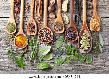 Spices and herbs on a wooden background - stock photo