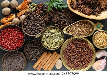 Spices and herbs on black ceramic  background. Food and cuisine ingredients. - stock photo