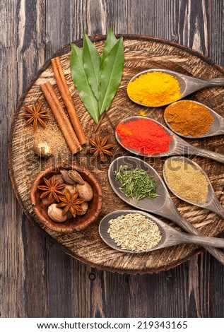 Spices and herbs on wooden board, close up - stock photo