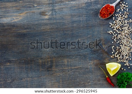 Spices and herbs over dark wood with space for text. Food and cuisine ingredients. - stock photo