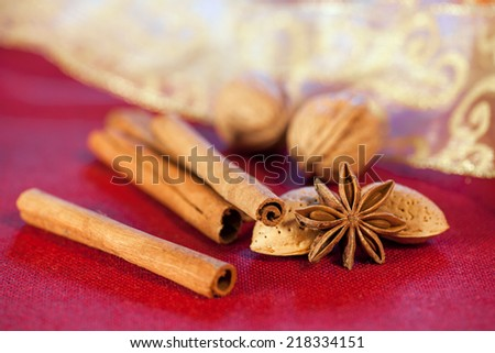 Spices and ingredients for baking christmas cookies, cinnamon, anise, walnuts, almonds on red background. - stock photo