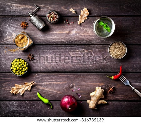 Spices and ingredients for the dish on the wooden background with space for text - stock photo