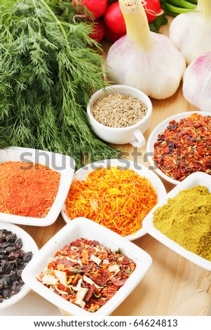 Spices and vegetables on wooden board selective focus - stock photo
