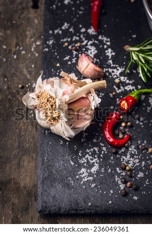 Spices background with garlic,red chili,herbs,salt and pepper on dark slate background - stock photo
