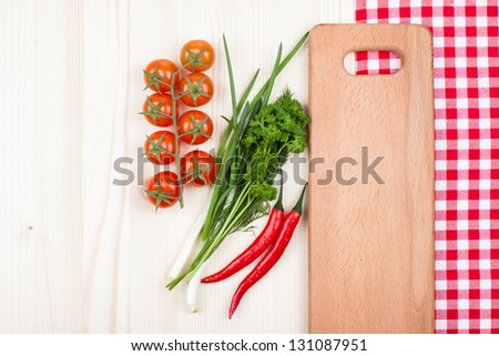 Spices, cherry tomatoes, chili, tablecloth, plank on wood background - stock photo