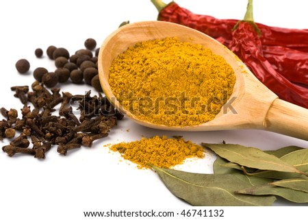 spices: curry in wooden spoon, pepper, pimento, cloves and bay leaves on white background