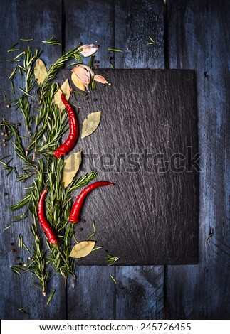 Spices food background with slate on blue wooden table, top view, place for text - stock photo