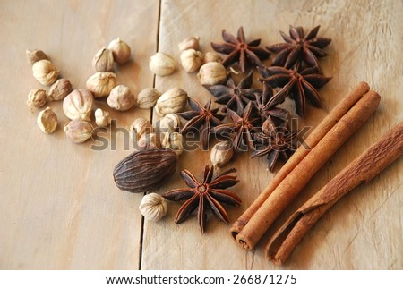 spices for chinese food boiled include anise; cardamom; cinnamon; placed on the wooden background - stock photo