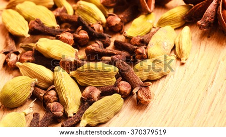 Spices for christmas cakes cardamom anise stars and cloves on wooden table surface - stock photo