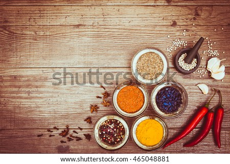 Spices for cooking meat: turmeric, chili pepper, barberry on the wooden background. Top view. Sepia toned. Copy space left. Horizontal.