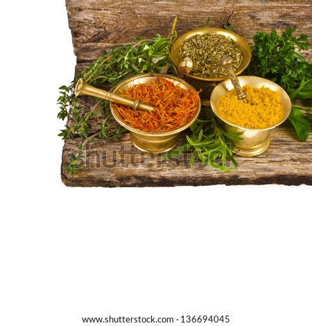 Spices for the kitchen - dry oregano, saffron and mix in three copper mortar and fresh sprigs of herbs isolated on white background - stock photo