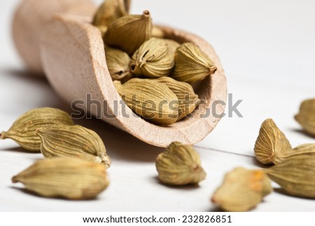 Spices. Green dried cardamon on white wooden table. - stock photo