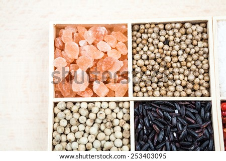 Spices (himalayan salt, coriander and white pepper) and black rice in a wooden box - stock photo
