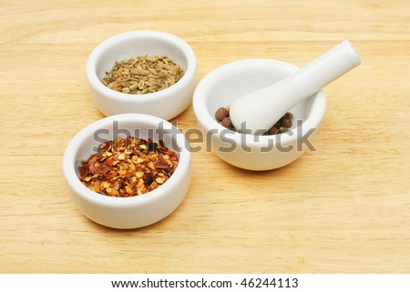 Spices in a ramekins and a pestle and mortar