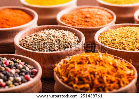 spices in a wooden bowl close-up on a brown background