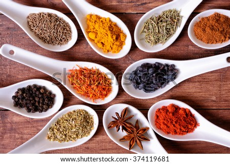 Spices in ceramic bowls on wooden background.