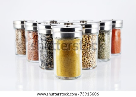 Spices in glass bottles, arranged one in front of another.