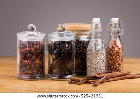 spices in glass bottles on wooden background