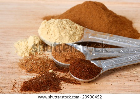 Spices in measuring spoons on a wooden cutting board - stock photo