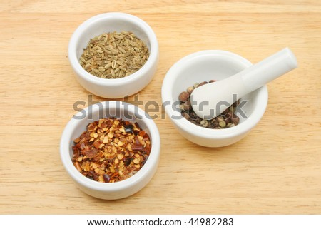 Spices in small pots and pestle and mortar