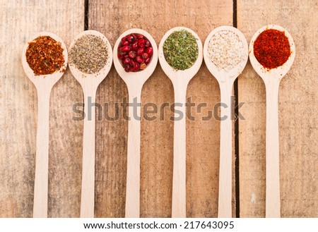 Spices in spoon on wooden background - stock photo