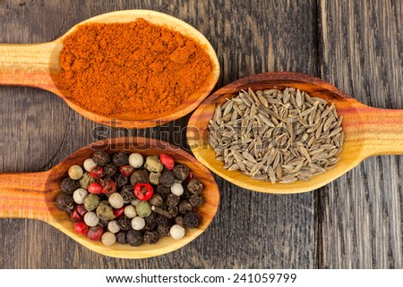 spices in spoons on wooden background - stock photo