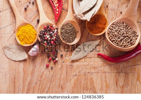 spices in the spoons on a wooden table - stock photo