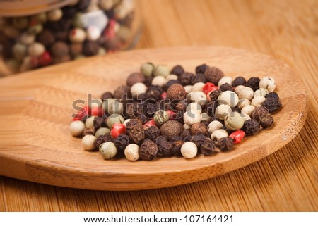 spices in wooden spoon and pepper