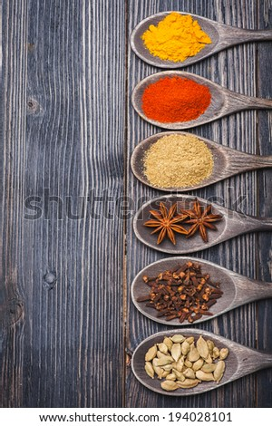 Spices in wooden spoons. Chili powder, turmeric, masala, cardamom, coriander, star anise  - stock photo