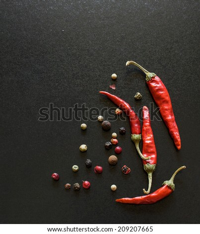 Spices on a blackboard .Chili pepper , bay leaves and allspice