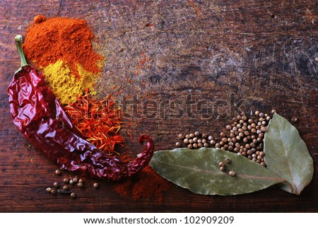 Spices on a old wooden cutting board with saffron, curry and chili pepper - stock photo