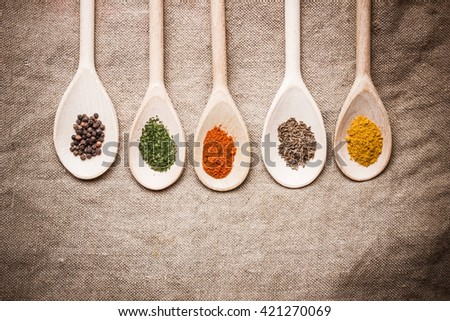 Spices on old wooden spoons. Linen fabric background.