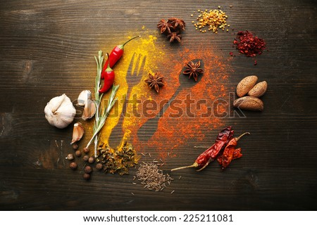 Spices on table with cutlery silhouette, close-up  - stock photo