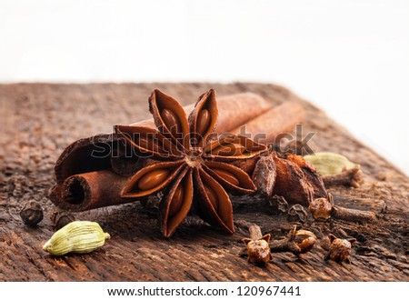 Spices on wooden table on white background - stock photo