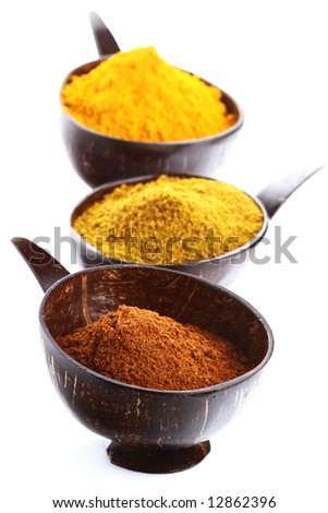 spices - pile of bright Madras Curry Powder and 2 bowls behind, shallow DOF - stock photo